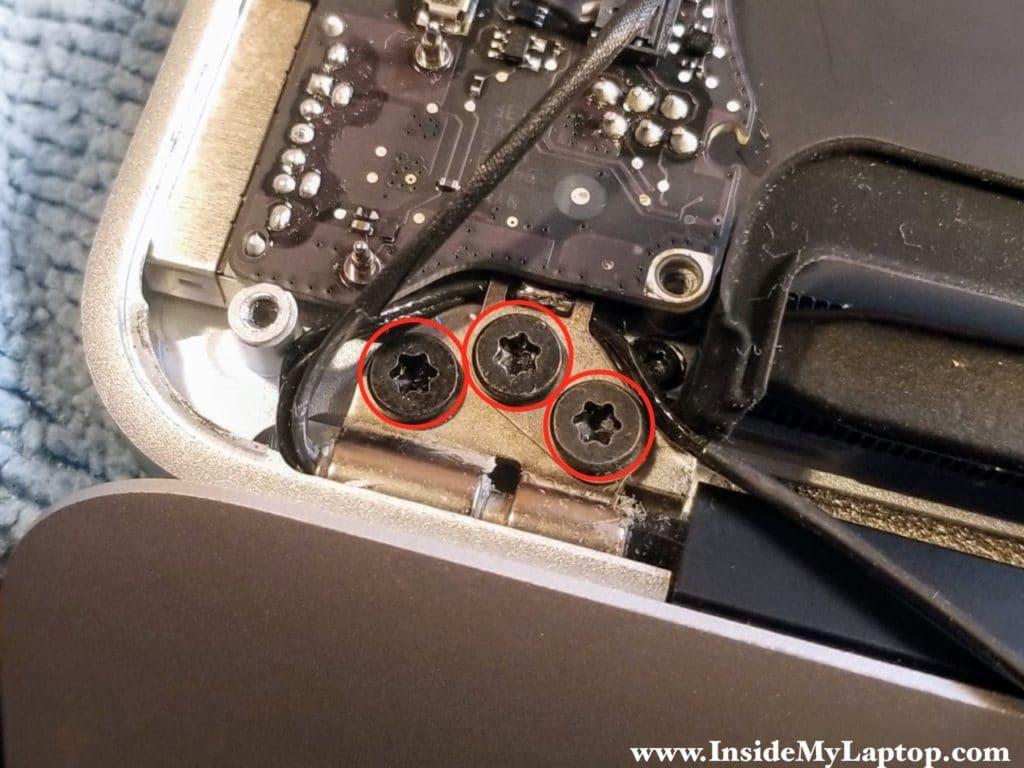 Three screws securing left hinge