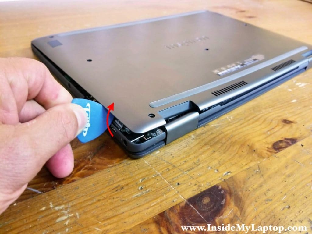 Using a thin case opener tool start separating the base cover from the palmrest assembly.