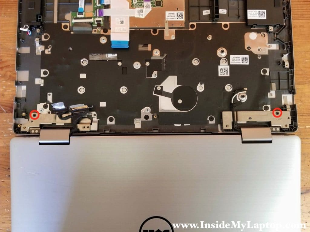 Open the display panel 180 degrees. Remove two screws securing the left and right display hinges.