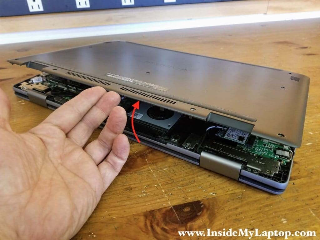 Start separating the base cover from the top case assembly on the rear side of the laptop.
