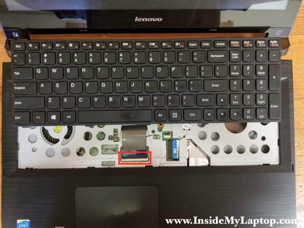 Move the keyboard towards the display panel in order to access the cable connector underneath.