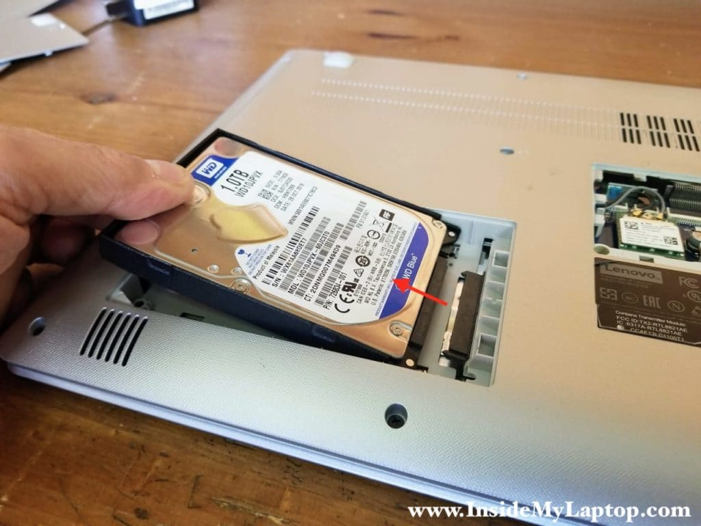 Lift up the left side of the hard drive and pull it to the left to disconnect from the SATA port on the motherboard.