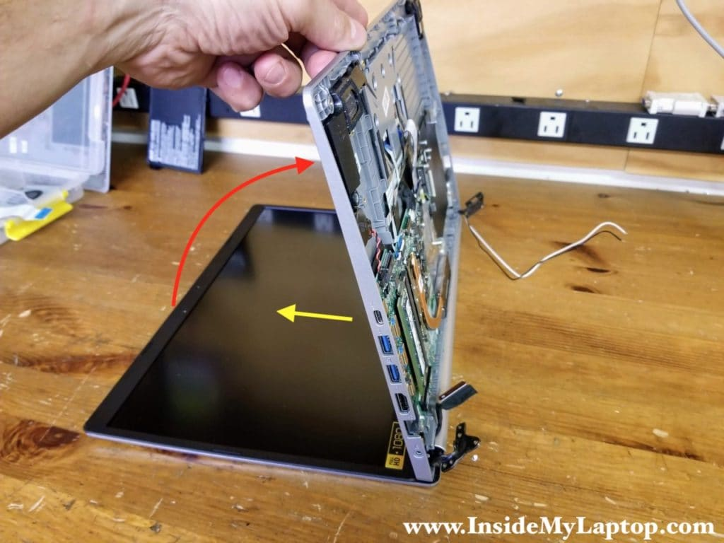 Lift up one side of the top case assembly and slide it from under the display hinges.