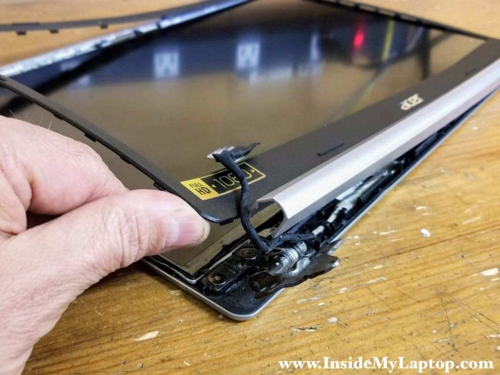 Lift up one side of the screen bezel and separate it from the hinge.