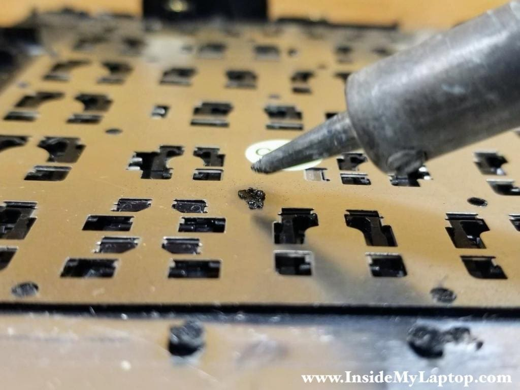 "While applying pressure on the keyboard, melt the rivet so a new ""head"" is created and it secures the keyboard."