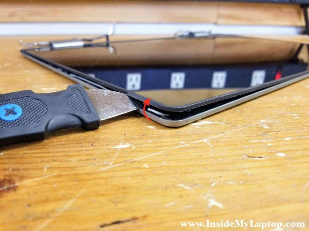 Start separating the touchscreen assembly from the display back cover using a thin case opener tool.