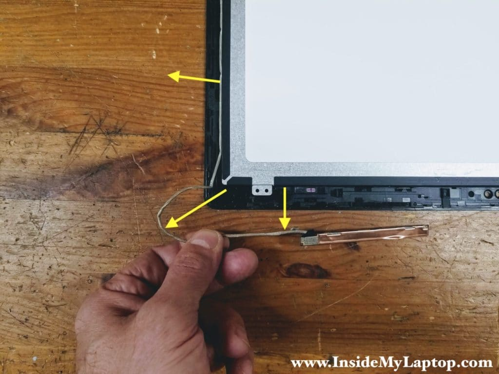 Un-route the webcam cable from the guided path on the left side of the touchscreen assembly.